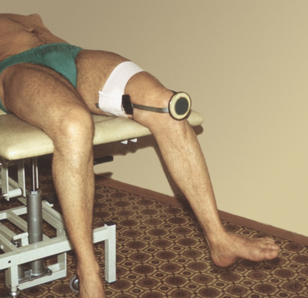 Рис. 8д). Измерение амплитуды движений в тазобедренном суставе: измерение внутренней ротации левого бедра с помощью ротатометра, обе бранши которого установлены вдоль оси бедра