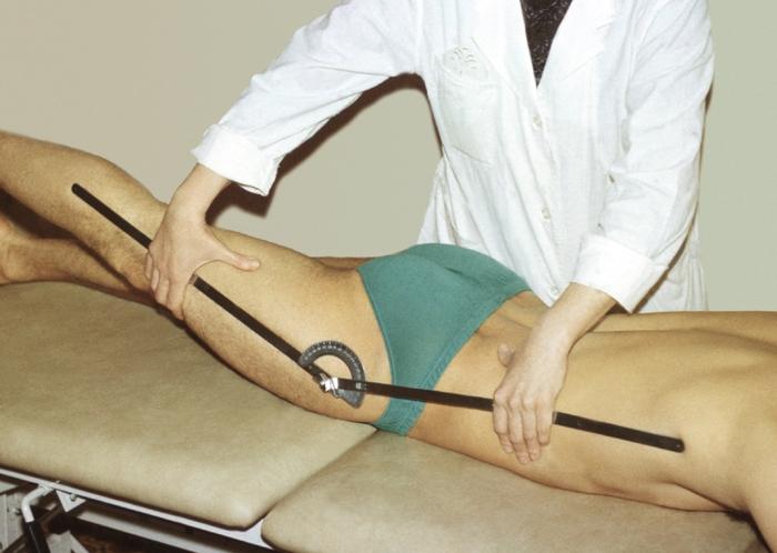 Рис. 8б). Измерение амплитуды движений в тазобедренном суставе: разгибание бедра; одна бранша гониометра совмещена со средней подмышечной линией, другая — с продольной осью бедра; шарнир гониометра расположен в области верхушки большого вертела