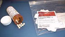 Little white pills on a counter, next to a pill bottle and labels
